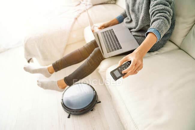 Сверху вид на урожай женщины в повседневной одежде с помощью пульта дистанционного управления для роботизированного пылесоса, сидя на диване и наслаждаясь свободным временем просмотра Интернета на ноутбуке — стоковое фото
