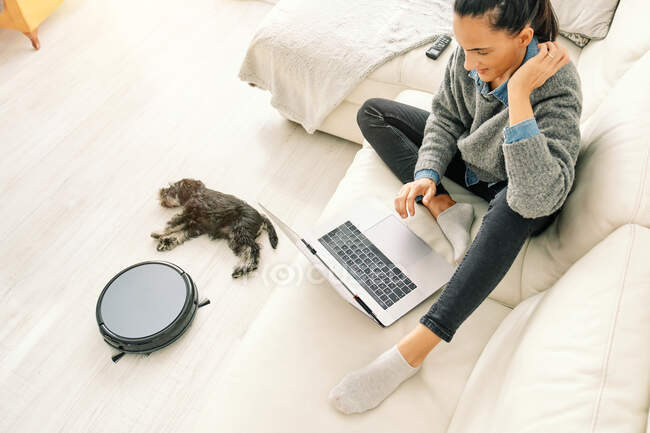 From above woman sitting on sofa in light room with cute puppy lying down next round black robotic vacuum cleaner — Stock Photo