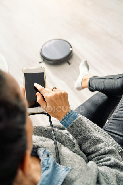 From above of crop person in casual clothes using mobile app and controlling robotic vacuum cleaner while sitting in room with light wooden floor — Stock Photo