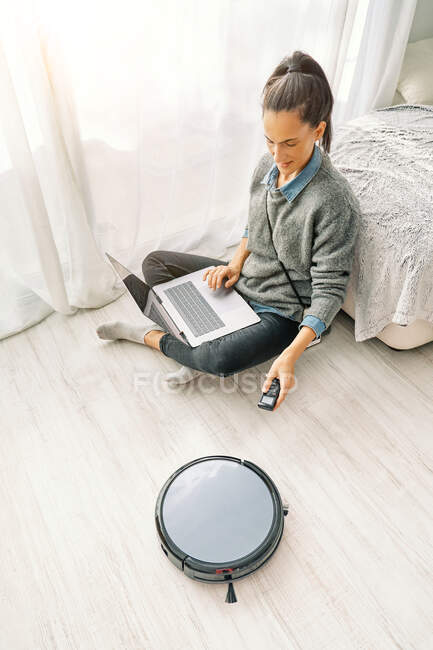 From above woman in casual clothes using remote control for robotic vacuum cleaner while sitting on sofa and enjoying free time browsing internet on laptop — Stock Photo