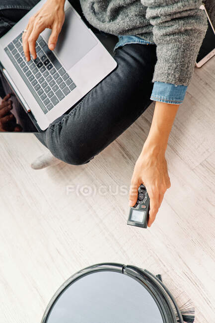 From above side view of crop female in casual clothes using remote control for robotic vacuum cleaner while sitting on sofa and enjoying free time browsing internet on laptop — Stock Photo