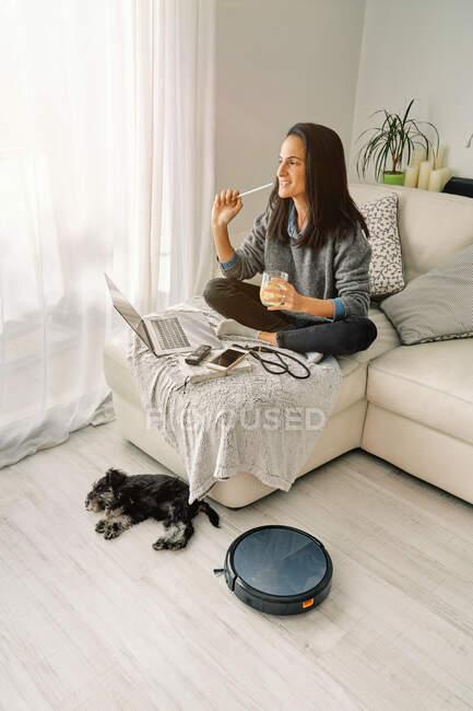 Mujer sentada en un sofá en una sala de luz trabajando en una computadora y bebiendo bebida fría con un lindo cachorro acostado al lado de la aspiradora robótica negra redonda - foto de stock
