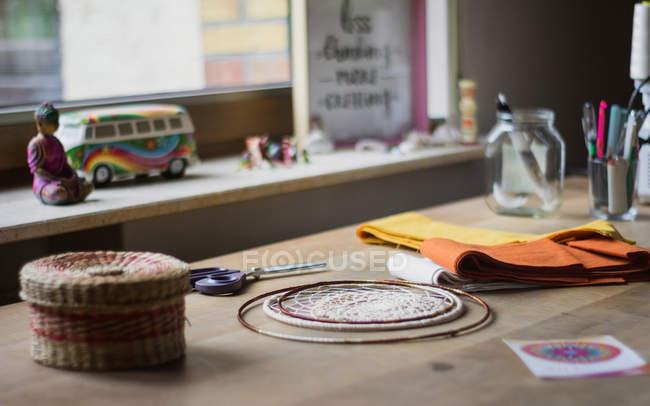 Local de trabalho para a criação de sonhador artesanal com fios e acessórios e tesouras perto com soleira em casa — Fotografia de Stock