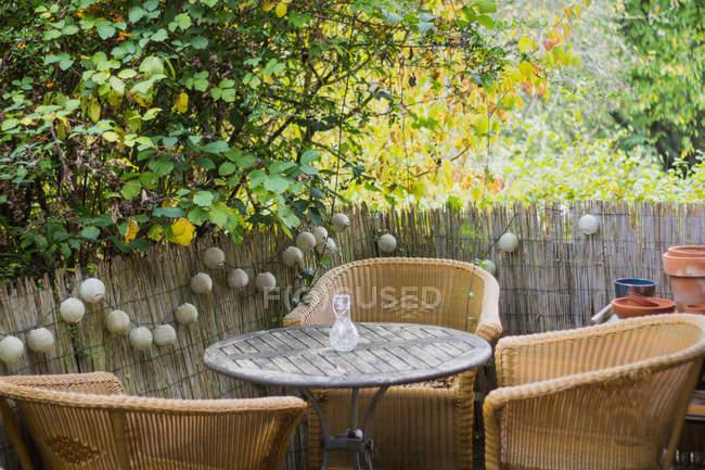 Espace douillet pour se détendre avec des fauteuils confortables en osier et une table dans un jardin moderne par une journée ensoleillée. — Photo de stock