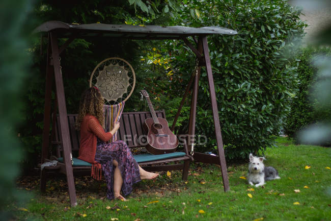 Vue latérale d'une agricultrice regardant un attrape-rêves fait à la main avec de longs fils assis sur une balançoire en bois dans la cour arrière — Photo de stock