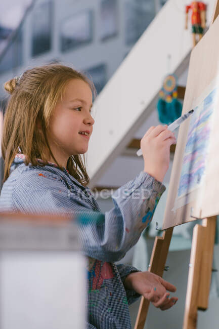Happy child drawing on canvas — Stock Photo