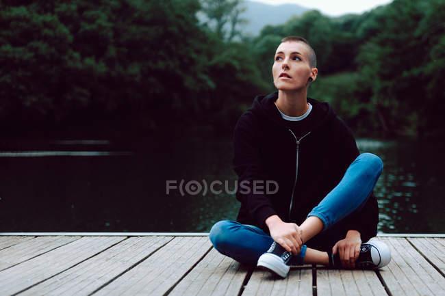 Hipster femminile con acconciatura corta in abbigliamento casual seduta con gambe incrociate su pontile di legno di stagno con alberi verdi su sfondo sfocato — Foto stock