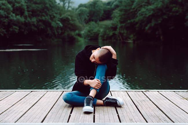 Самка гіпстер з короткою зачіскою в повсякденному одязі сидить зі схрещеними ногами на дерев'яному пірсі ставка з зеленими деревами на розмитому фоні. — стокове фото