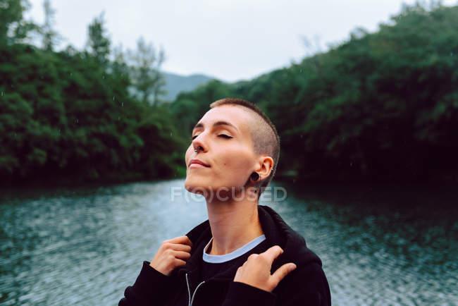 Femme à coiffure courte percée de vêtements décontractés face à face, les yeux fermés vers le ciel, avec étang au milieu de plantes vertes sur fond flou — Photo de stock