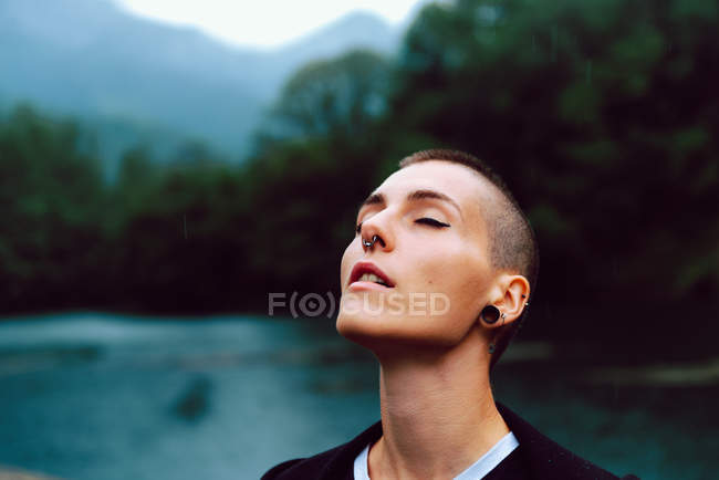 Woman with short hairstyle and piercing in casual clothing facing head up with closed eyes to sky with pond among green plants on blurred background — Stock Photo