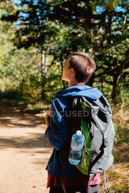 Vista posteriore del turista femminile con zaino che ha viaggio e camminare sulla strada rurale attraverso la foresta in estate — Foto stock
