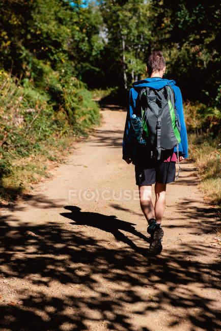 Vista posteriore del turista con zaino che ha viaggio e camminare sulla strada rurale attraverso la foresta in estate — Foto stock