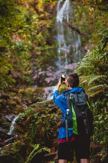Back view of woman with professional camera and backpack looking away while standing at waterfall in forest in summer day — Stock Photo
