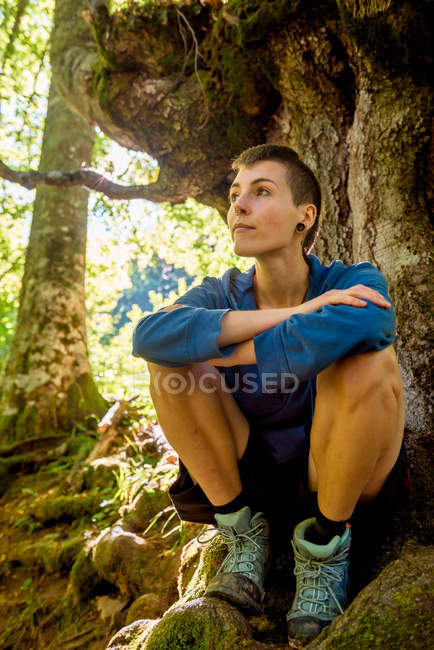 Peaceful young woman in casual clothes enjoying nature and sitting under tree in forest in summertime — Stock Photo