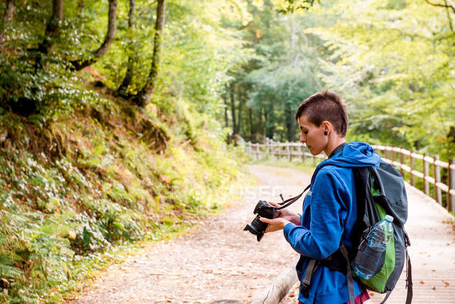 Serious youthful female hiker enjoying vacation and taking picture on professional camera while standing on wooden pathway in forest — Stock Photo