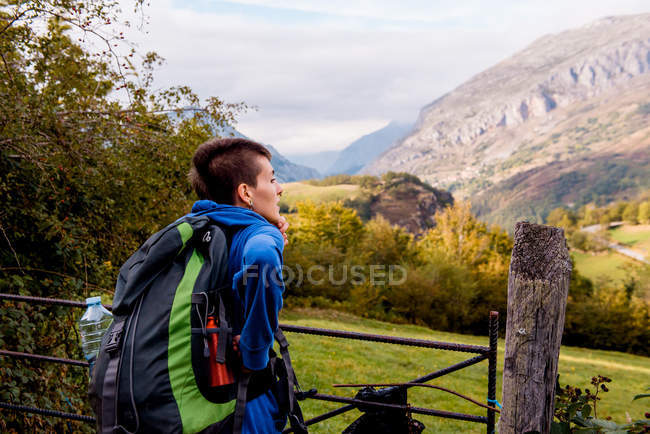 Back view of woman with backpack looking at nature and mountain landscape while standing at metallic gates in autumn day — Stock Photo