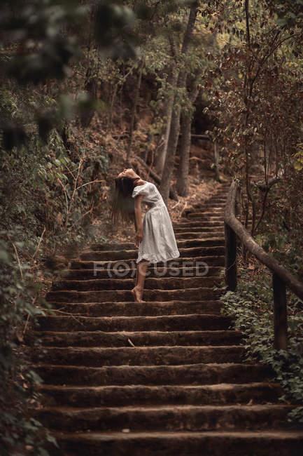Снизу таинственная спокойная женщина в белом платье наклоняется головой, стоя на лестнице в тихом осеннем парке — стоковое фото