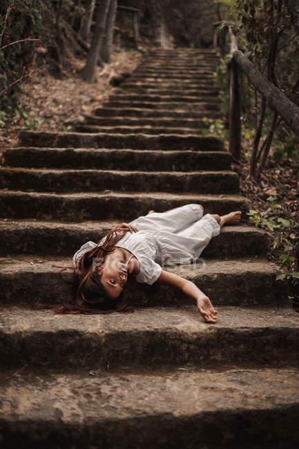 Dall'alto di tenera affascinante giovane donna in abito bianco sdraiato vulnerabilmente sulle scale nel parco autunnale guardando altrove — Foto stock