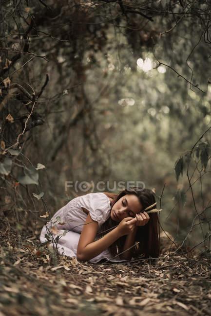 Чувственная таинственная женщина в белом платье сидит на коленях, прячась в осенней листве с закрытыми глазами — стоковое фото