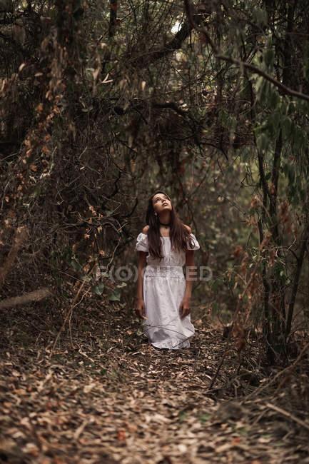 Таинственная спокойная женщина в белом платье, стоящая в тихом осеннем парке — стоковое фото
