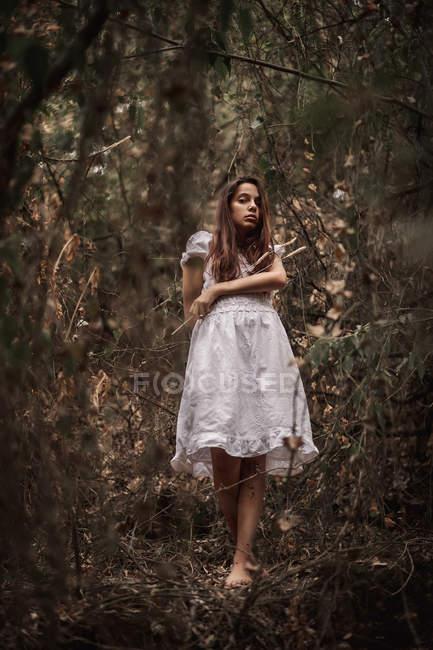 Mulher calma misteriosa em vestido branco em pé no parque outonal calma — Fotografia de Stock