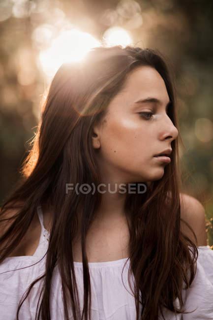 Боковой вид на нежную великолепную молодую женщину в белом платье, обнимающую плечи, стоящую в спокойном парке и отворачивающуюся — стоковое фото