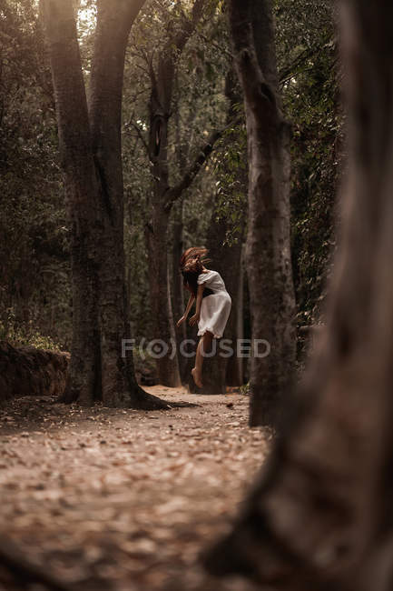 Misteriosa mujer tranquila en vestido blanco saltando levitando en tranquilo parque otoñal - foto de stock