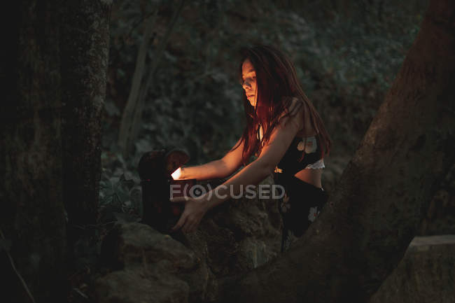 From below of young woman in dress taking ancient retro clock in wooden box on stone in autumnal forest — Stock Photo