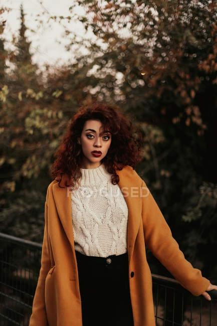 Женщина с темными кудрявыми волосами в трикотажном свитере и пальто, стоящие в парке, кладущие руку на металлические перила, глядя в камеру — стоковое фото