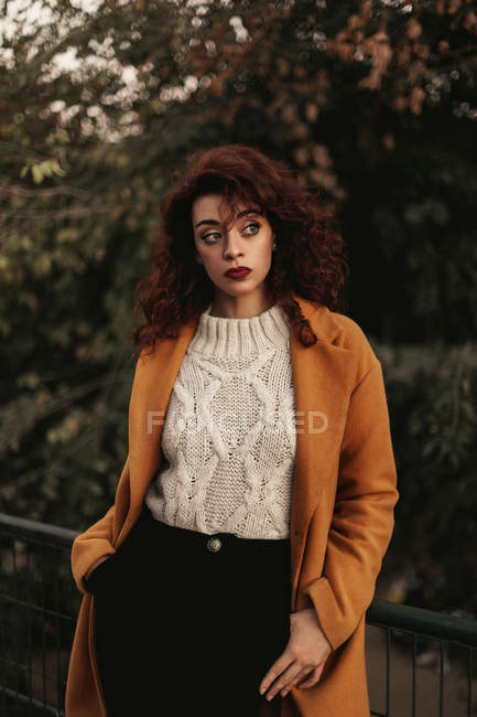 Woman with dark curly hair wearing knitted jumper and overcoat standing in park putting hand on metal railing while looking at camera — Stock Photo