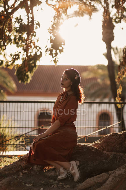 Woman in beret wearing romantic vintage clothes and shoes sitting on stone with crossed legs in back lit and looking away — Stock Photo
