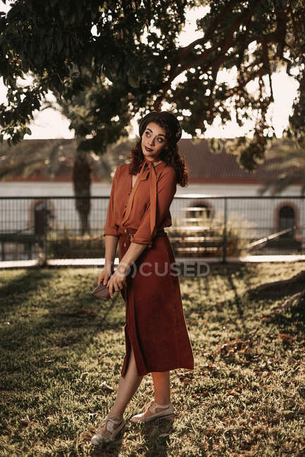 Woman in romantic vintage blouse and skirt standing in crossed graceful pose on grass holding book in hands — Stock Photo