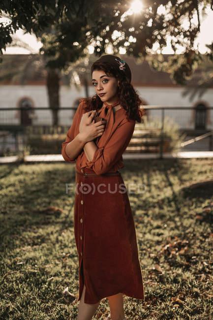Женщина в романтической винтажной блузке и юбке, стоящая в скрещенной изящной позе на траве, держа в руках книгу — стоковое фото