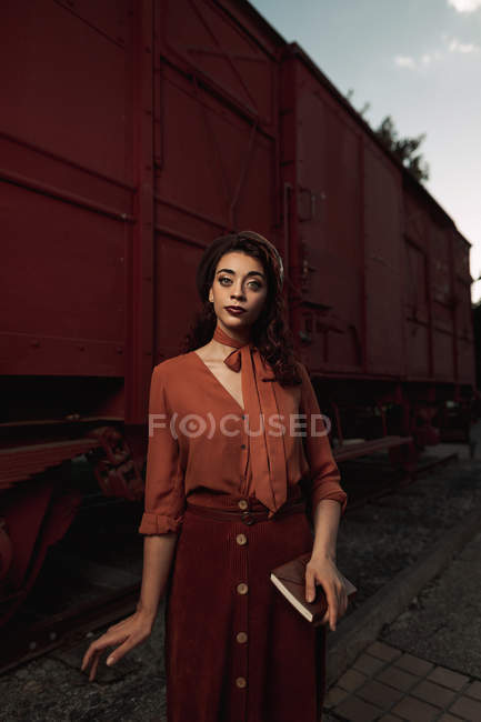 Frau in Terrakottakleidung im Vintage-Stil steht in der Nähe von Terrakottabahn und hält aufgeschlagenes Buch in Händen — Stockfoto