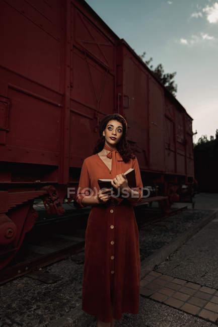 Frau ganz in Terrakottakleidung im Vintage-Stil steht in der Nähe von Terrakottabahn und hält aufgeschlagenes Buch in Händen — Stockfoto