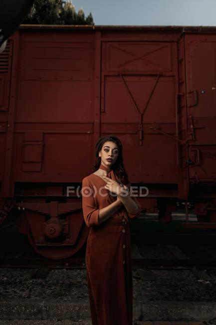 Donna che indossa abiti in terracotta in stile vintage in piedi vicino treno auto in terracotta e tenendo aperto libro — Foto stock