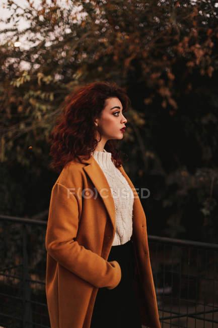 Donna con capelli ricci scuri che indossa maglione lavorato a maglia e cappotto in piedi nel parco mettendo mano su ringhiera metallica mentre guarda altrove — Foto stock
