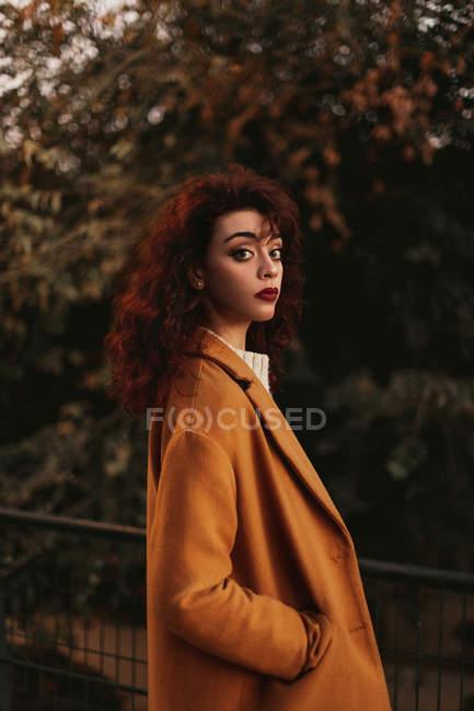 Donna con i capelli ricci scuri indossa maglione a maglia e cappotto in piedi nel parco mettendo mano su ringhiera metallica mentre guarda la fotocamera — Foto stock
