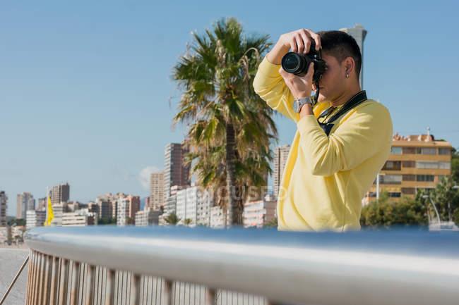 Jeune photographe inspiré en sweat-shirt décontracté jaune parlant photo sur la caméra debout sur le quai de la ville au soleil — Photo de stock
