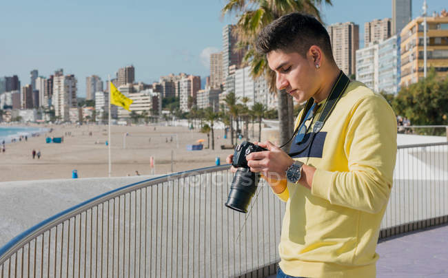 Creative young photographer shooting on waterfront — Stock Photo