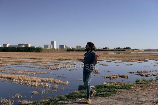 Man standing in front of lake on shore among short yellow lakeside grass pretending to play guitar with hands looking away — Stock Photo