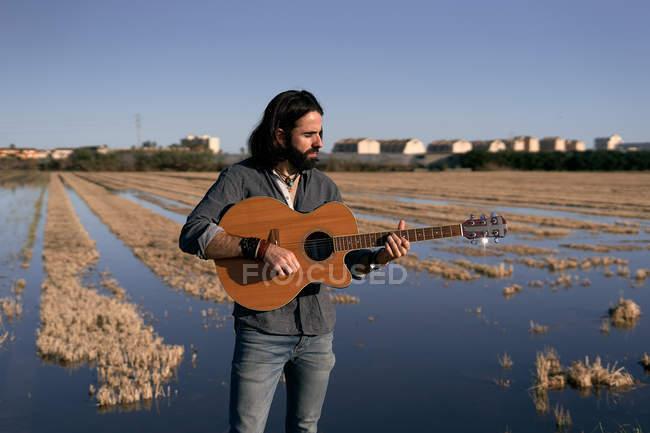 Langhaariger Musiker mit Bart, der mit Gitarre am Seeufer steht und auf den Hals schaut, während er mit Hütten über dem See als Hintergrund spielt — Stockfoto