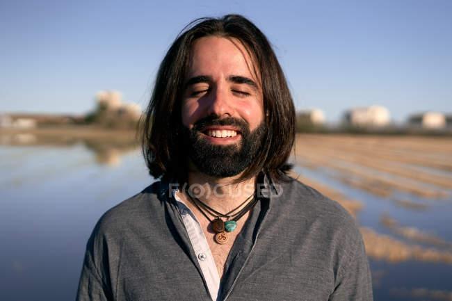 Hombre de pie frente al lago en la orilla entre la hierba amarilla corta junto al lago con los ojos cerrados y una sonrisa - foto de stock