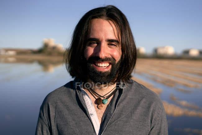 Hombre de pie frente al lago en la orilla entre la hierba amarilla corta junto al lago mirando a la cámara con sonrisa - foto de stock