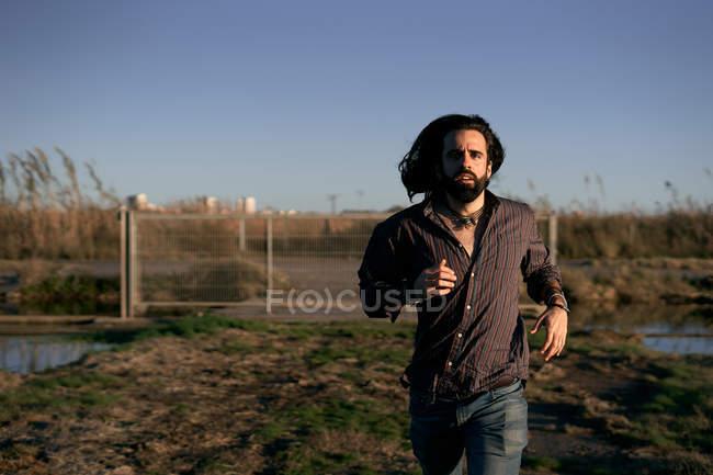 Homem de cabelos longos com barba na camisa e jeans fugindo da cidade através do portão e olhando para a câmera durante o dia — Fotografia de Stock