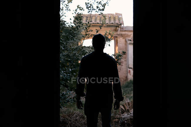 Back view of black silhouette of man standing in front of dark doorway facing shrubs and arc and looking forward in broad daylight — Stock Photo