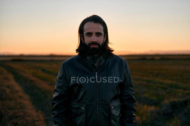 Homem com cabelos longos e barba em pé no meio do campo ao entardecer e olhando para a câmera com preocupação — Fotografia de Stock