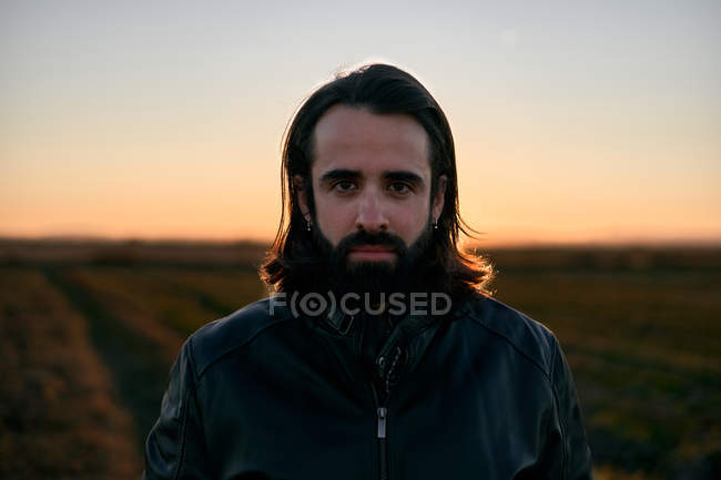 Man with long hair and beard standing in middle of field at dusk and looking at camera with concern — Stock Photo