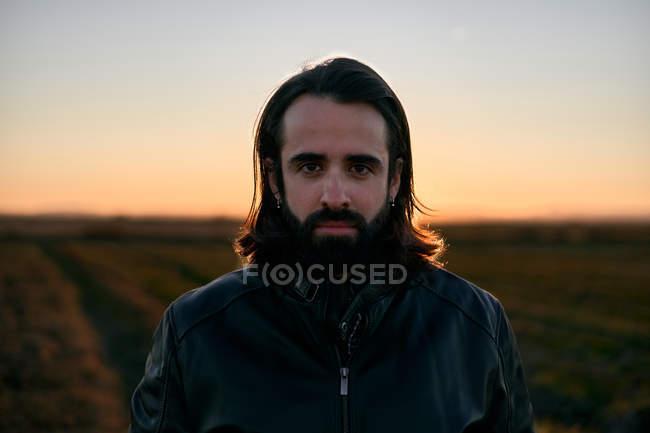 Mann mit langen Haaren und Bart steht in der Abenddämmerung mitten auf dem Feld und blickt besorgt in die Kamera — Stockfoto