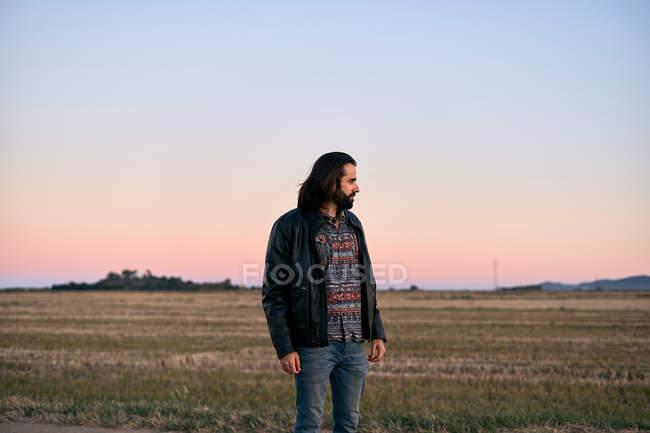 Homem com cabelos longos e barba em pé no meio do campo ao entardecer e olhando para longe com preocupação — Fotografia de Stock